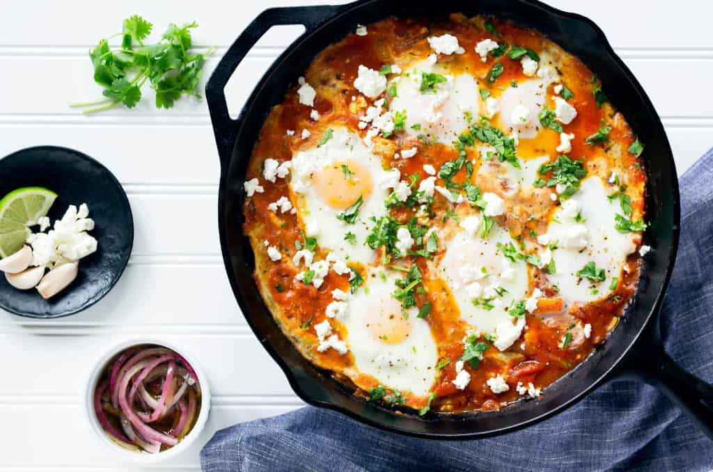 easy shakshuka recipe in a cast iron skillet with cilantro and feta