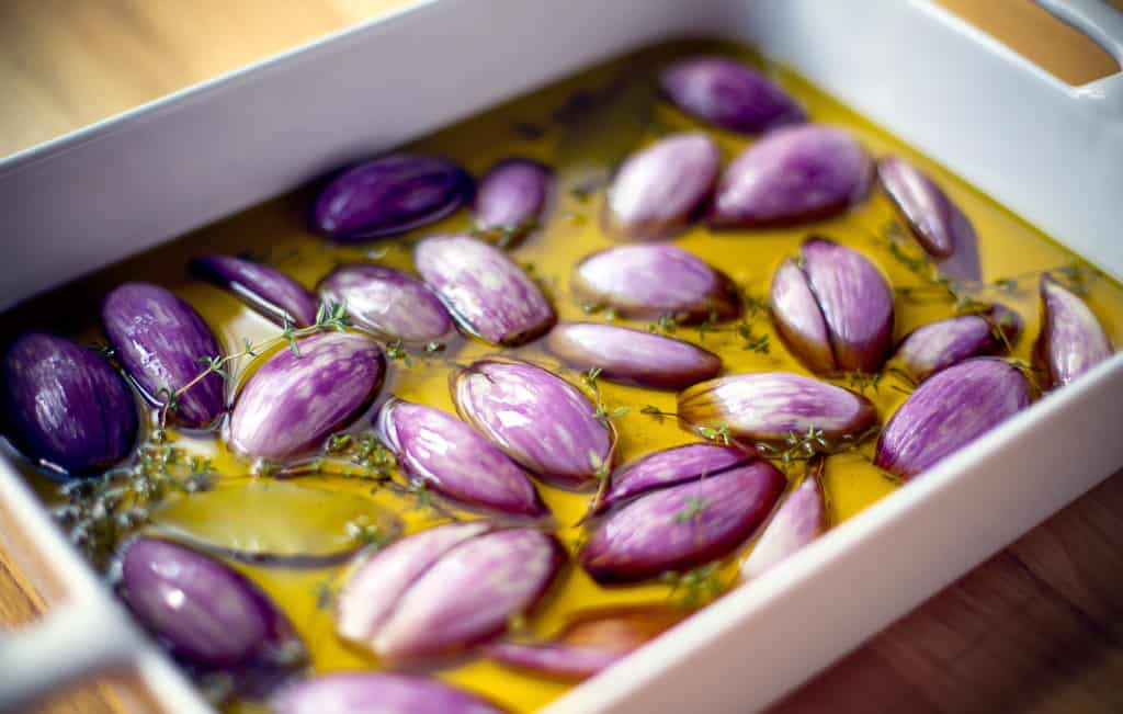 shallots confit in a large white baking dish
