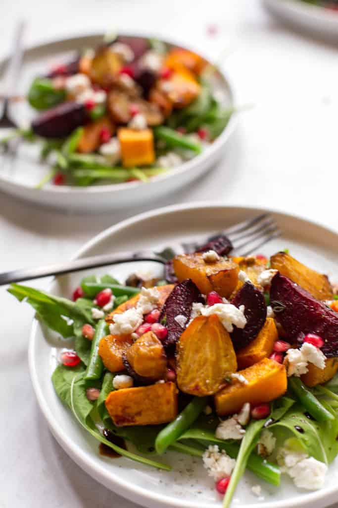 two white plates filled with arugula beet salad with butternut squash