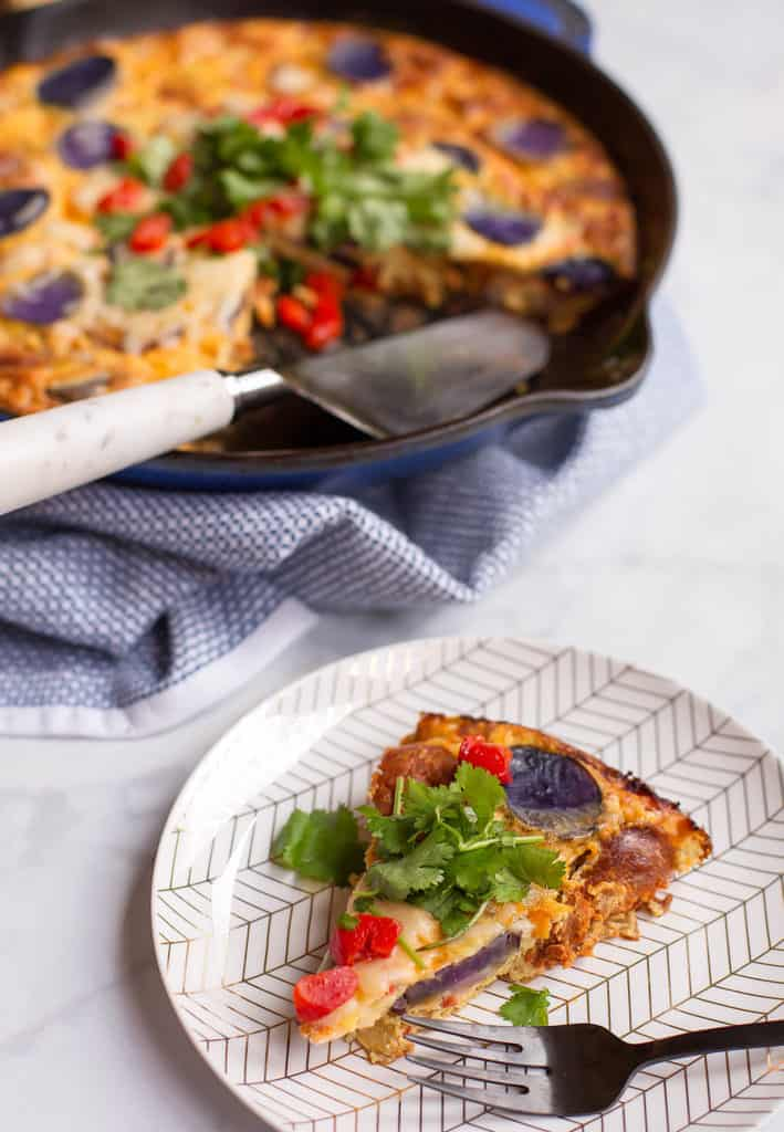 slice of chicken chorizo frittata with tomatoes and peppers on a white plate