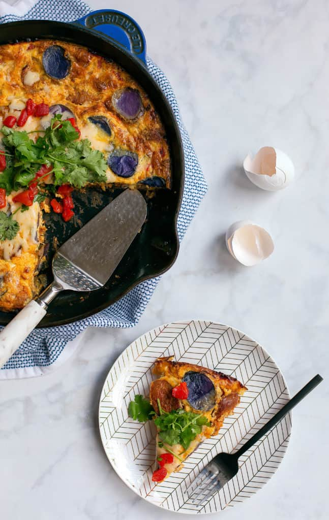 slice of chorizo frittata on a plate with potatoes and salad on top