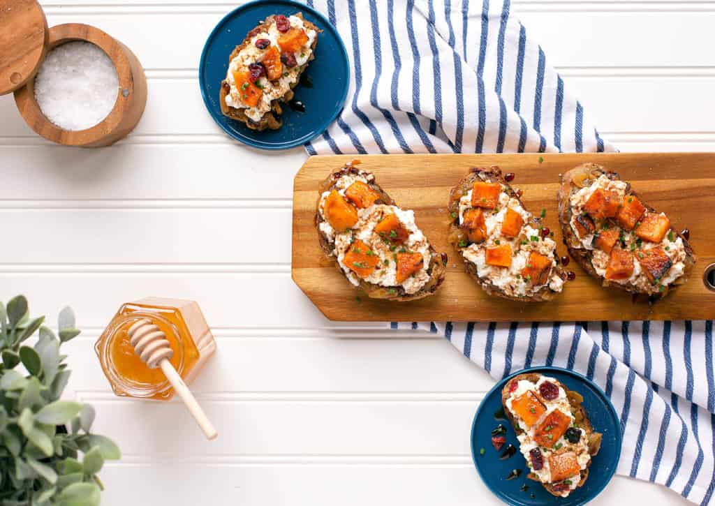 crostini with roasted butternut squash and whipped ricotta on blue plates and a wood serving tray