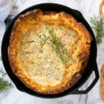 savory dutch baby with herbs and parmesan in a skillet with fresh thyme