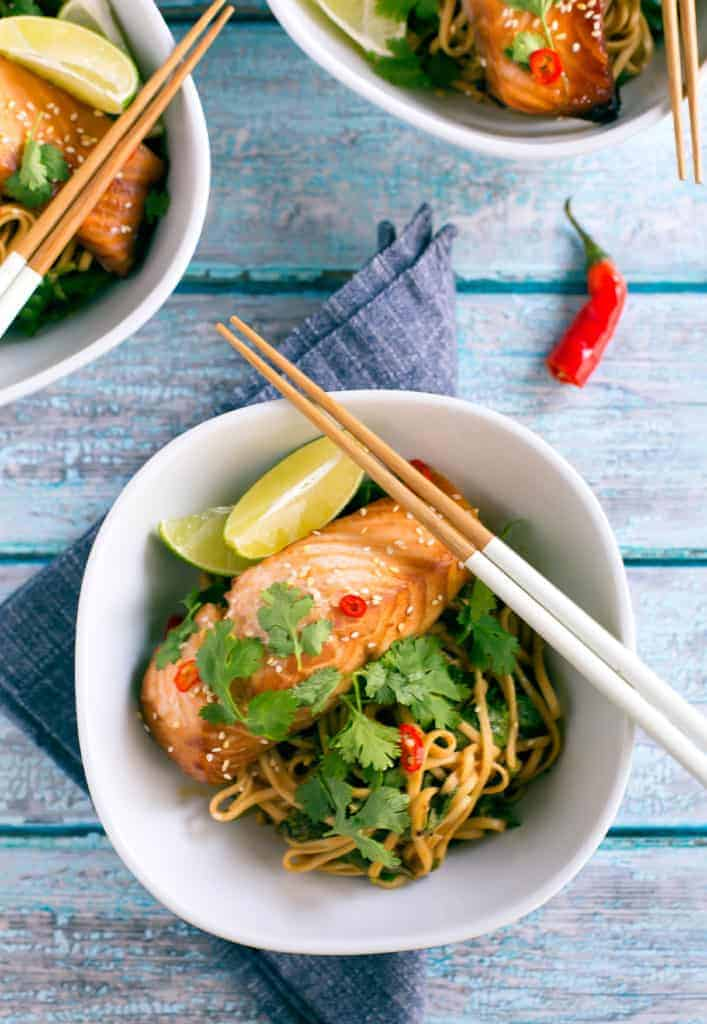 miso-marinated salmon bowl garnished with lime wedges and cilantro