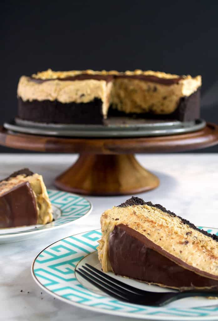 chocolate peanut butter tart on a wood cake stand with slices on a few teal plates