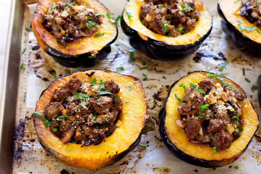 acorn squash with sausage stuffing on baking tray