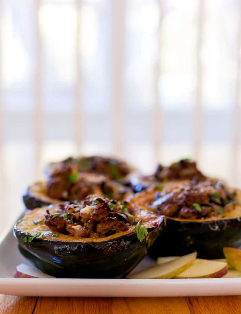 sausage stuffed acorn squash on white platter with apple slices