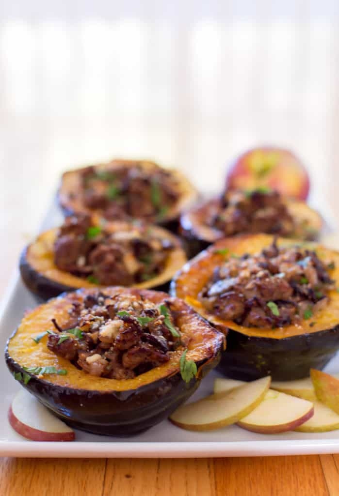 Sausage stuffed acorn squash on white platter with apple
