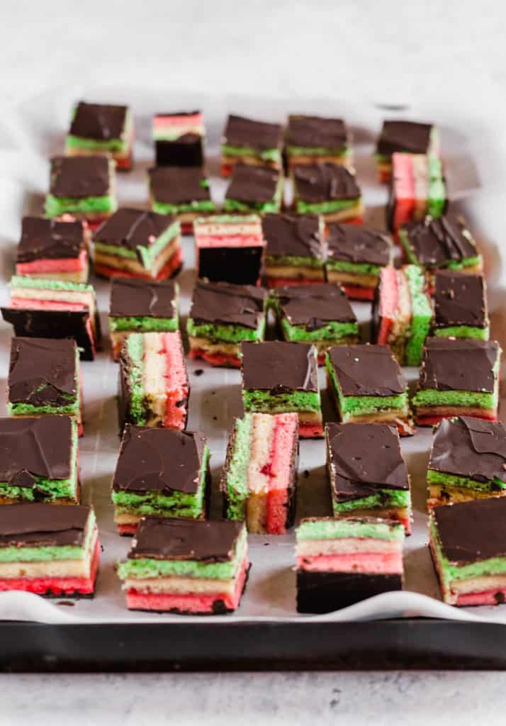 Italian rainbow cookies on parchment paper-lined baking tray