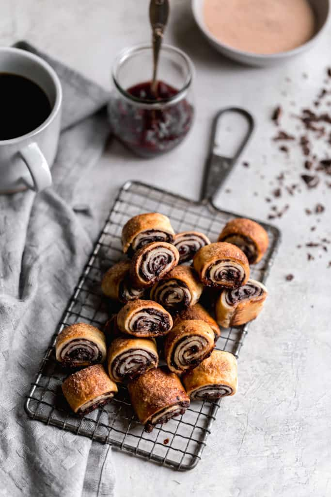 chocolate raspberry rugelach on a cookie tray with chocolate shavings on the board