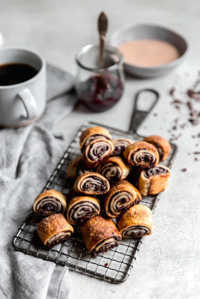 raspberry and chocolate rugelach on a serving tray with coffee and jam in the background