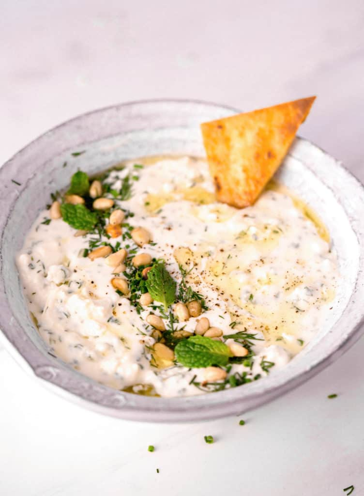 pita chip being dipped into homemade whipped feta dip in a white bowl