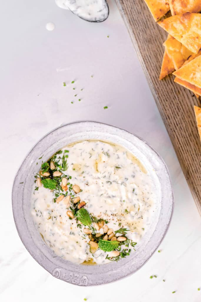 feta cheese dip in white bowl with homemade pita chips