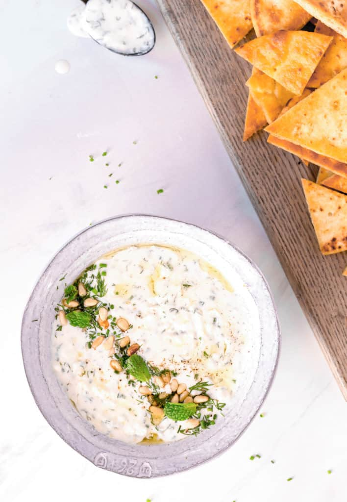 creamy whipped feta dip in a white bowl with homemade pita chips next to it