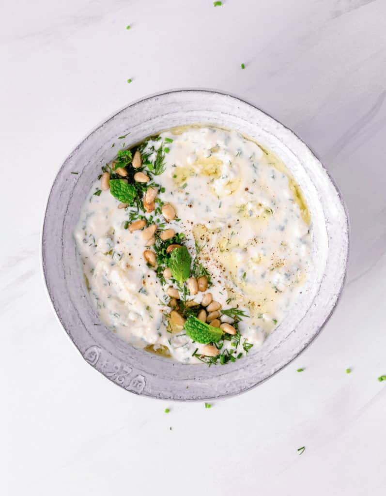 whipped feta dip in a white bowl with herbs and toasted pine nuts on top