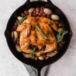 whole roast chicken in a cast iron skillet with rosemary grapes and shallots