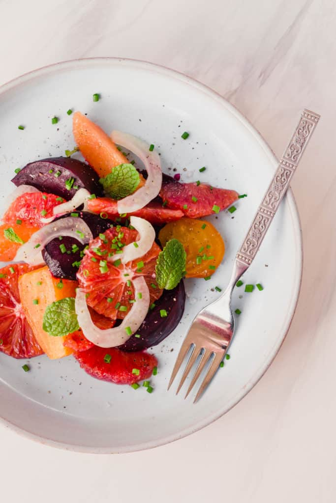 winter citrus salad with roast beets and fennel on a blue plate with fork