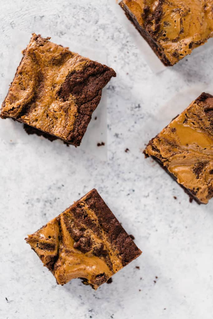 chocolate peanut butter brownie squares on a marble board