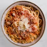 pork sugo over pasta in a large bowl with shaved parmesan on top