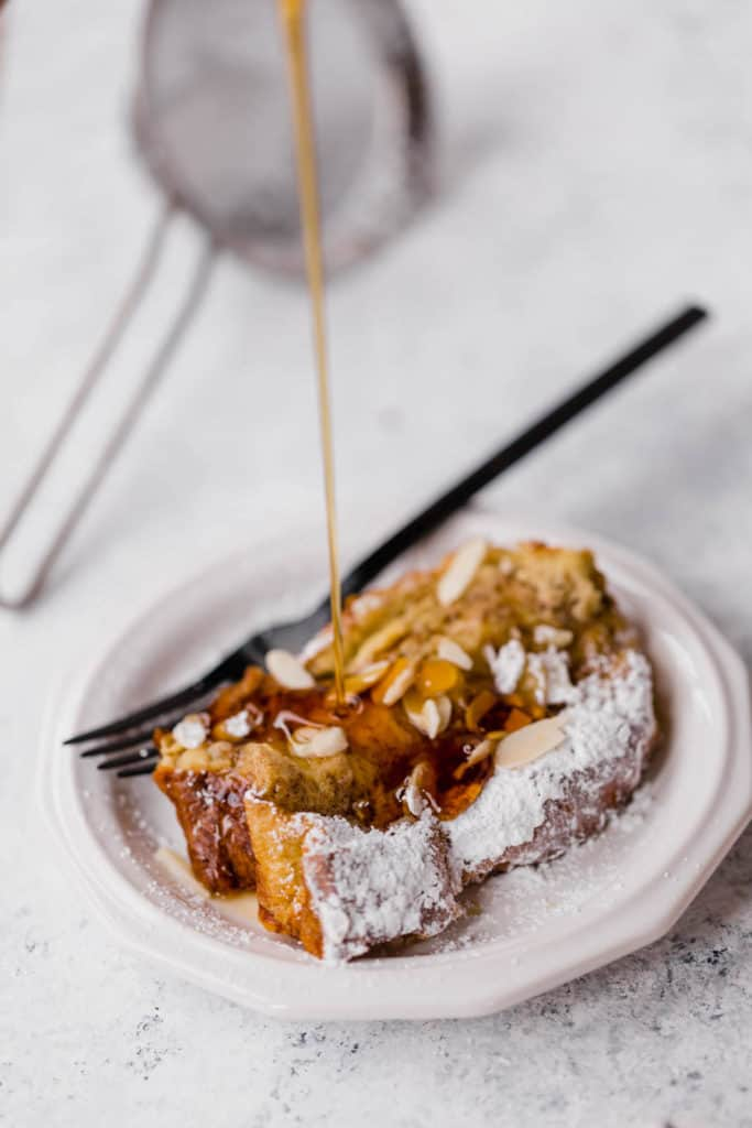 warm maple syrup being poured on top of a slice of baked french toast on a white plate with a black fork on the side