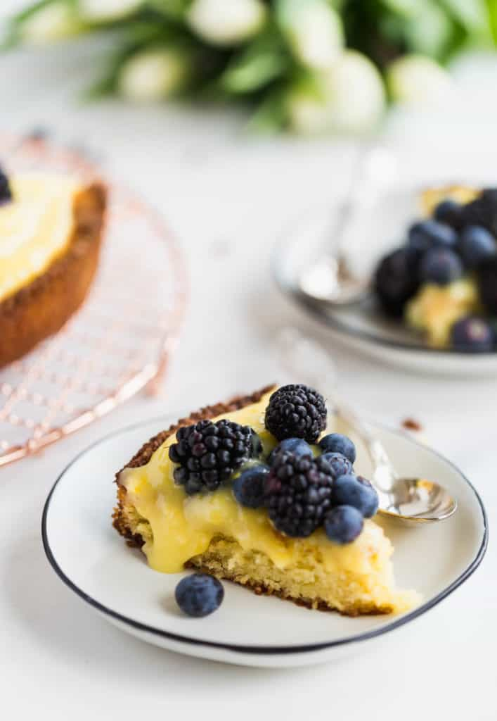 piece of almond cake with homemade lemon curd and fresh berries on a white plate