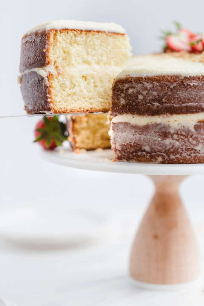 removing a slice of simple vanilla cake from cake stand