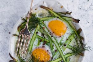 Creamy baked eggs with spring asparagus
