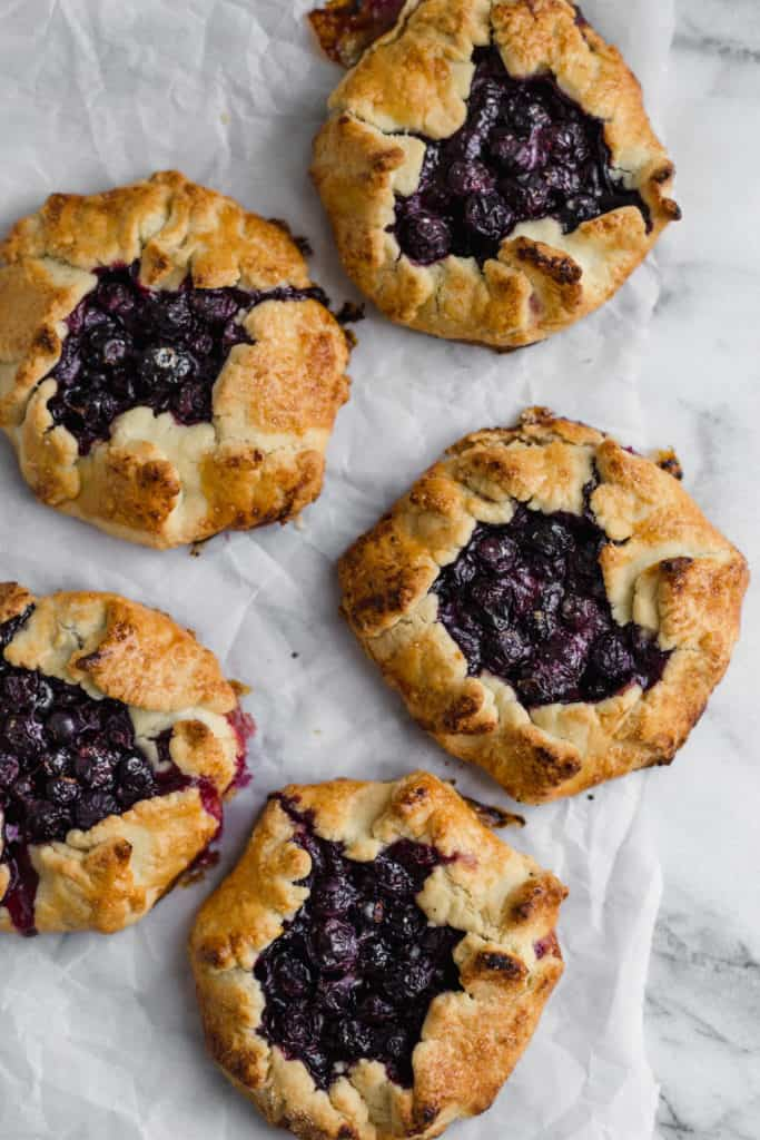 mini blueberry galettes on parchment paper