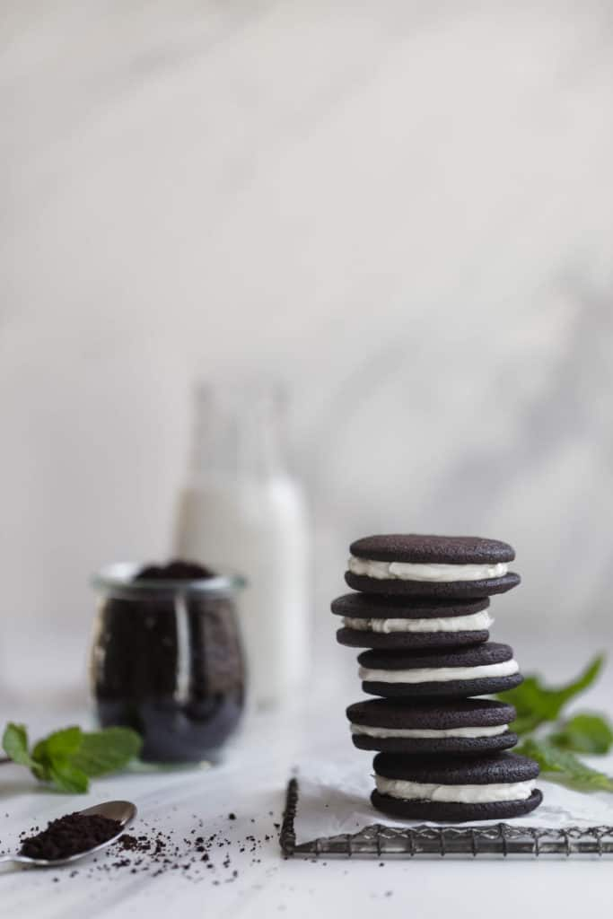 chocolate sandwich cookies on wire rack in front of pitcher of milk