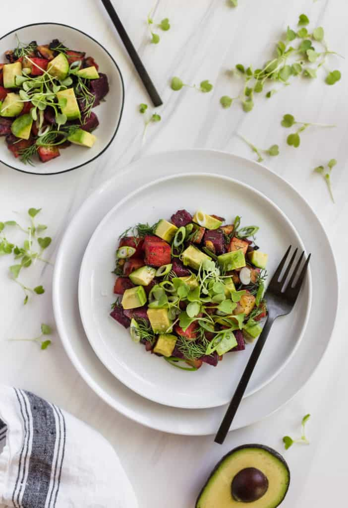 whole30 vegetable beet and avocado breakfast hash on a plate with black fork