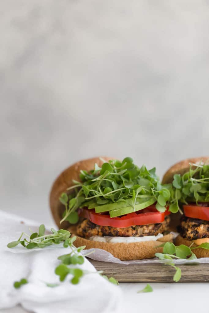homemade black bean burgers on a whole wheat bun with tomatoes, arugula, vocado, and tzatziki!