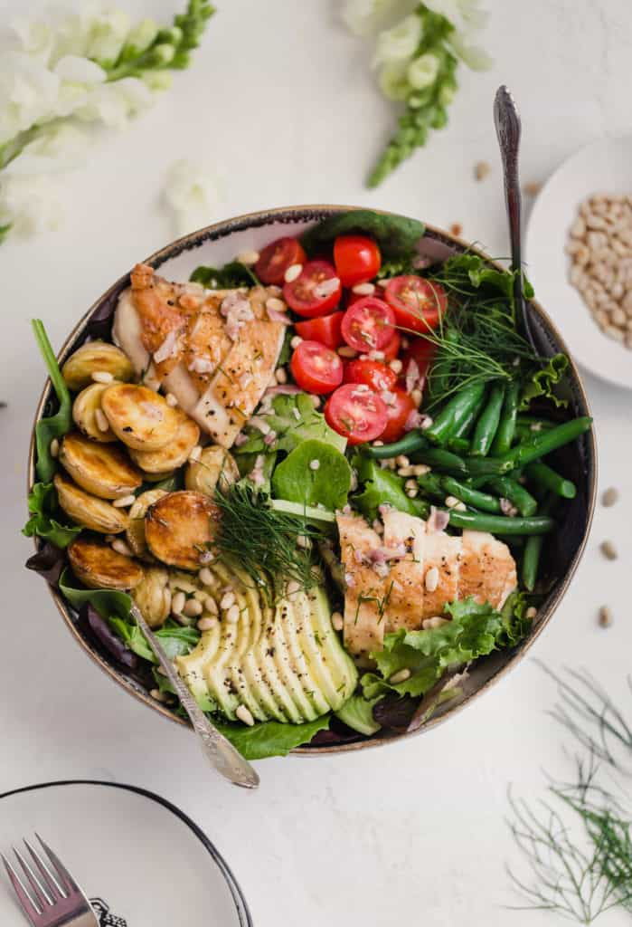 large dinner salad with roast chicken avocado roast potatoes tomatoes and green beans