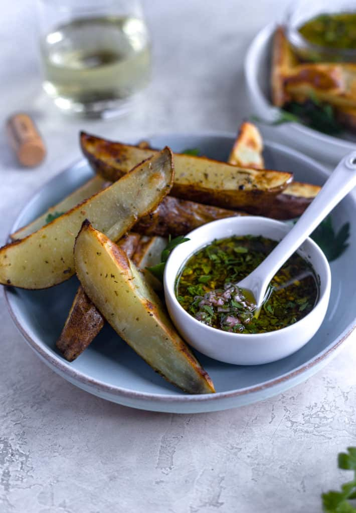 roasted potato wedges on white plate with pot of chimichurri sauce