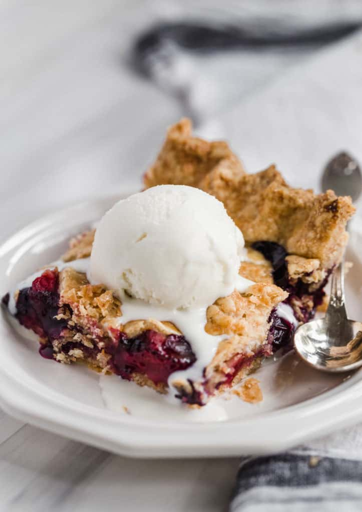 slice of triple berry pie topped with scoop of ice cream