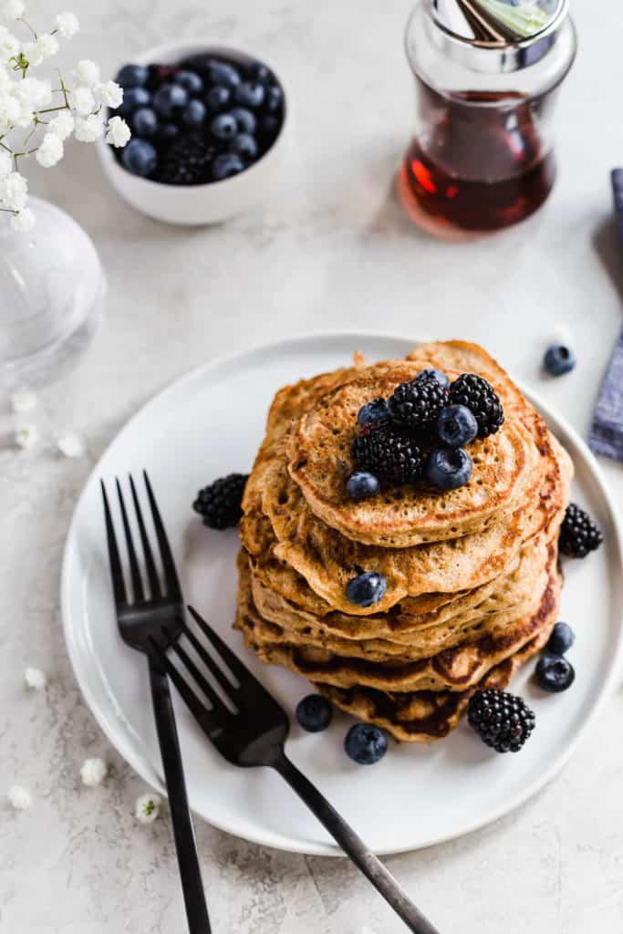 stack of oatmeal pancakes on a white plate with black forks