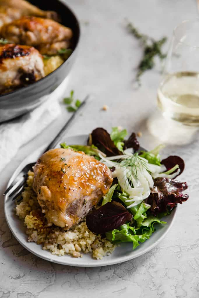 apricot chicken with couscous and side salad on a small plate