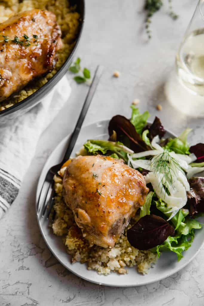 apricot chicken on a plate with cous cous and side salad