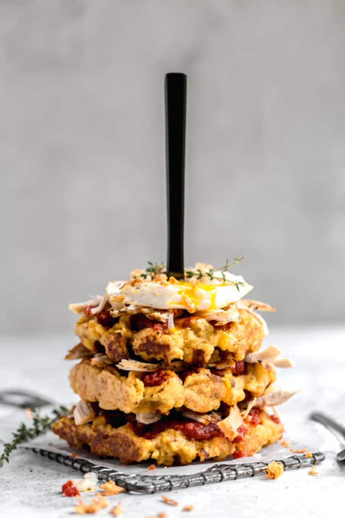 stack of three cornbread stuffing waffles with tomato jam, turkey, crispy onions, and a fried egg
