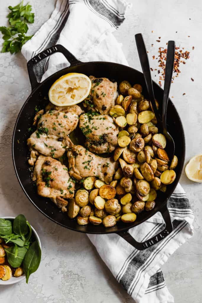 anchovy chicken and crispy potatoes in a cast iron skillet