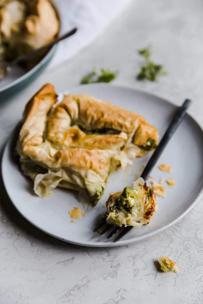 half eaten spanakopita spiral on a gray plate with a black fork