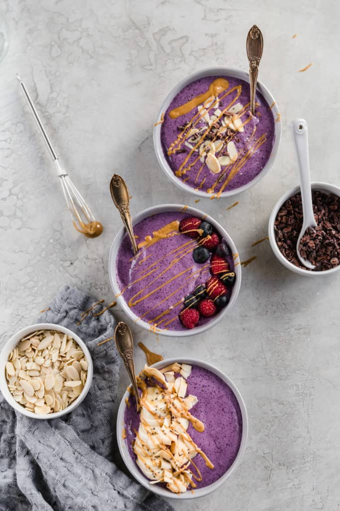 three peanut butter smoothie bowls with fruit on top