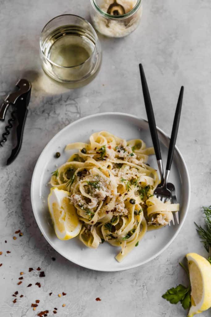 spicy crab pasta with lemon and capers on white plate with two forks