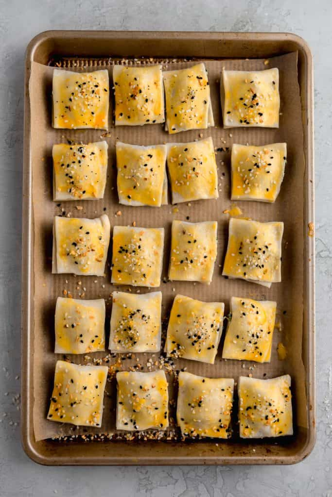 baking tray with 20 spinach and feta israeli bourekas before baking