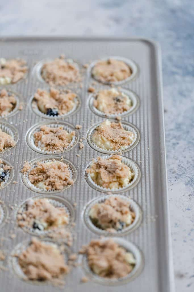 mini blueberry streusel muffins in muffin tin