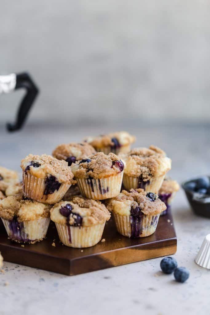 mini blueberry streusel muffins on wood platter