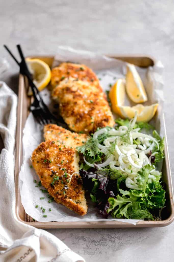 chicken milanese recipe breaded with panko breadcrumbs on a parchment lined baking sheet with shaved fennel salad on the side and lemon wedges