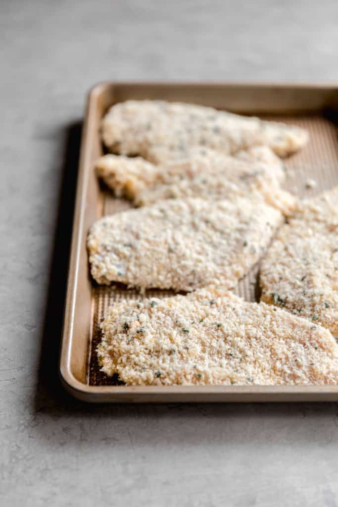 breaded chicken cutlets on a baking sheet before pan frying for chicken milanese recipe