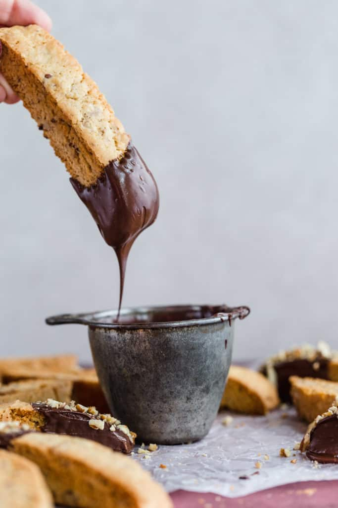 pecan biscotti being dipped into melted chocolate
