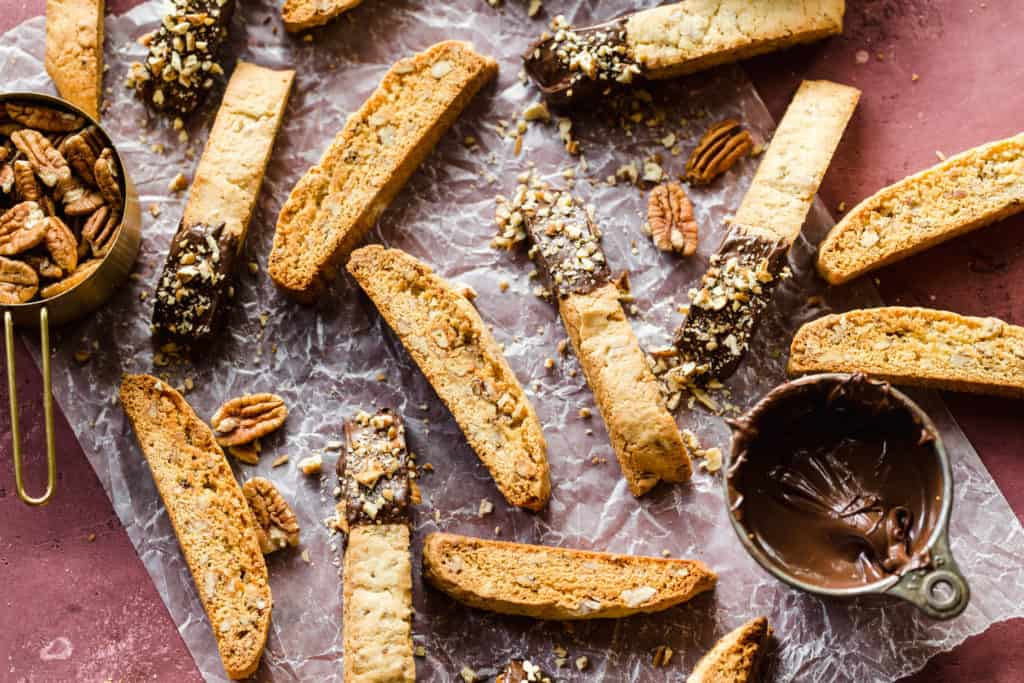 biscotti dipped in chocolate with crushed pecans sprinkled on