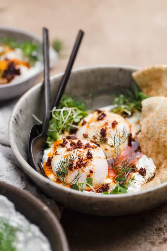 poached eggs on top of yogurt sauce in bowl with 'nduja